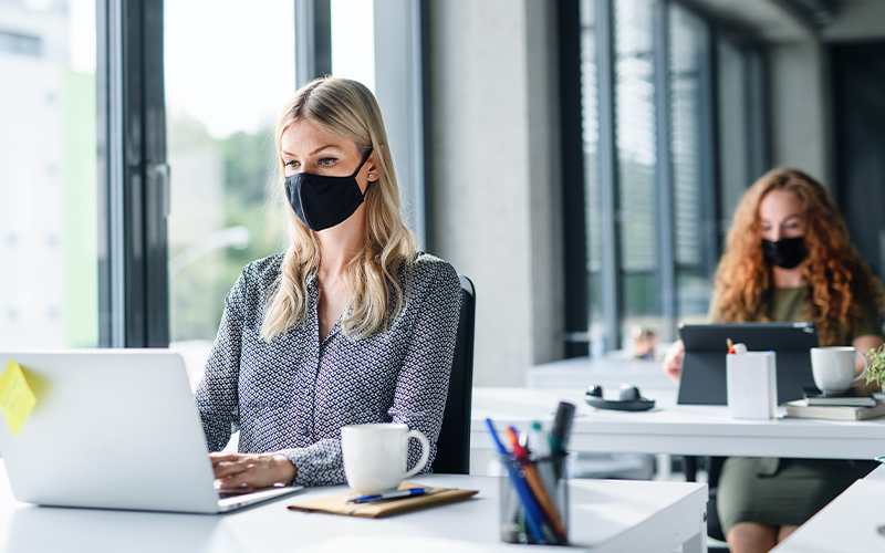 Woman sits at office desk with face mask on, with a colleague at a safe distance behind.