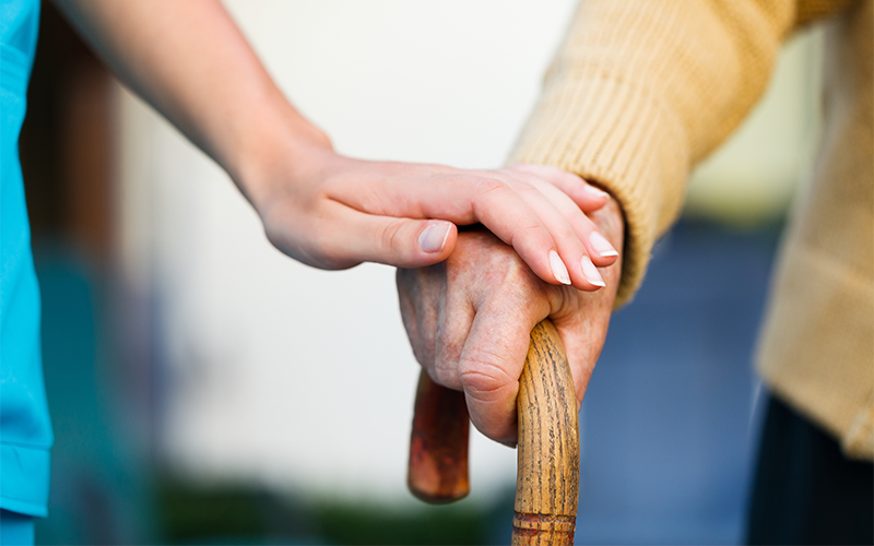 Elderly man uses walking stick, assisted by a carer.